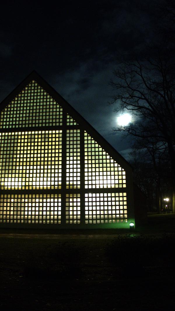Von innen beleuchtete Cornelius-Kirche, am Himmel der Vollmond