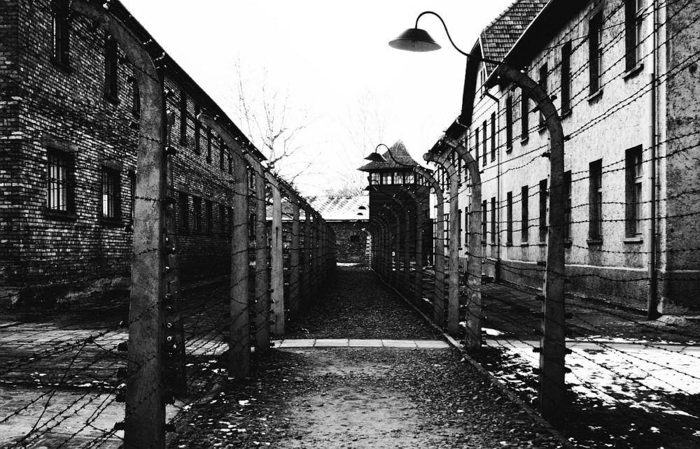 Ein gang zwischen Häusern und Stacheldrahtzäunen im KZ Auschwitz
