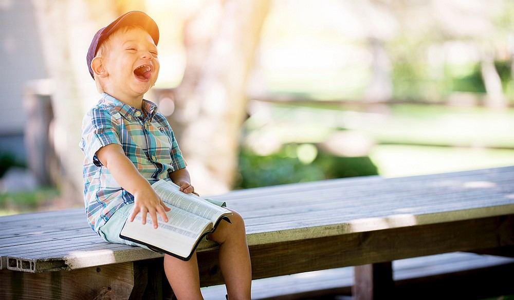 Ein Kind sitzt auf einer Bank, hält eine viel zu große Bibel und freut sich, ist stolz und lacht.