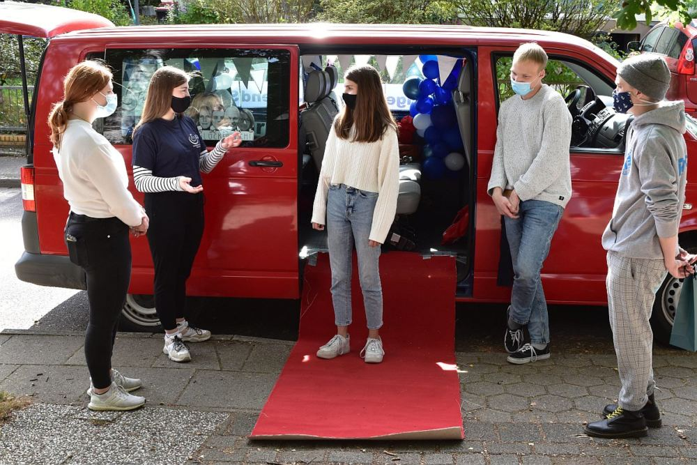 4 Teamer segnen eine Newcomerin auf einem roten Teppich vor einem Kleinbus.