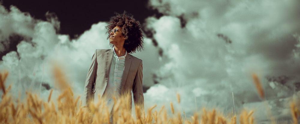 Ein Äthiopier mit langem krausen Haar, im Anzug und mit Sonnebrille steht in einem Kornfeld. Über ihm: Der Himmel