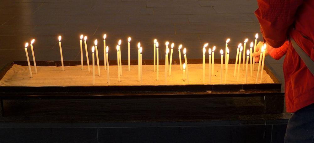 Eine Person mit roter Jacke steckt eine Kerze in das Kerzenbecken.