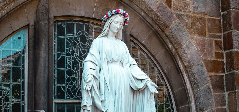 Bild einer Marienstatue aus weißem Marmor, sie ist mit einem bunten Blumenkranz geschmückt.