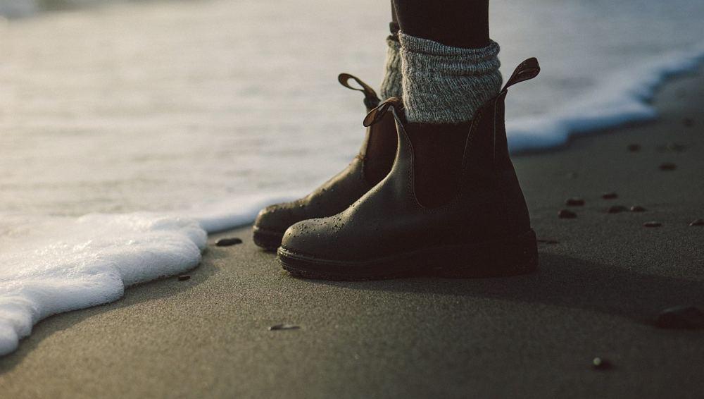 Gummistiefel, Wollsocken stehen am Schaumrand am Meer.