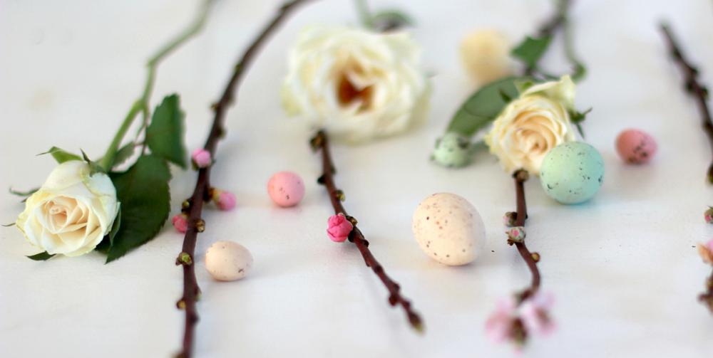 Stillleben aus zarten Rosen, kleinen Vogeleiern und Knospenden Apfelblüten