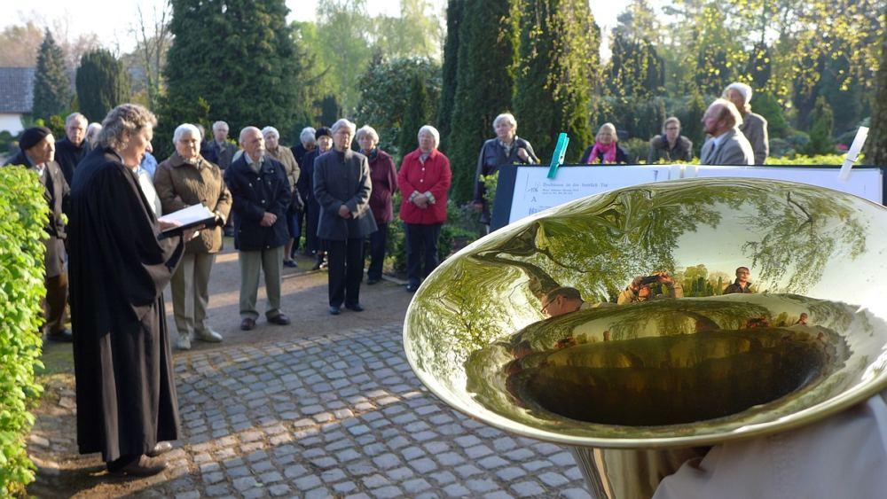Hier sieht man: Osterandacht auf dem Friedhof: Gemeinde, Pastor, Sonnenlicht über dem Friedhof und im Vordergrund groß und glänzend der Trichter einer Tuba.
