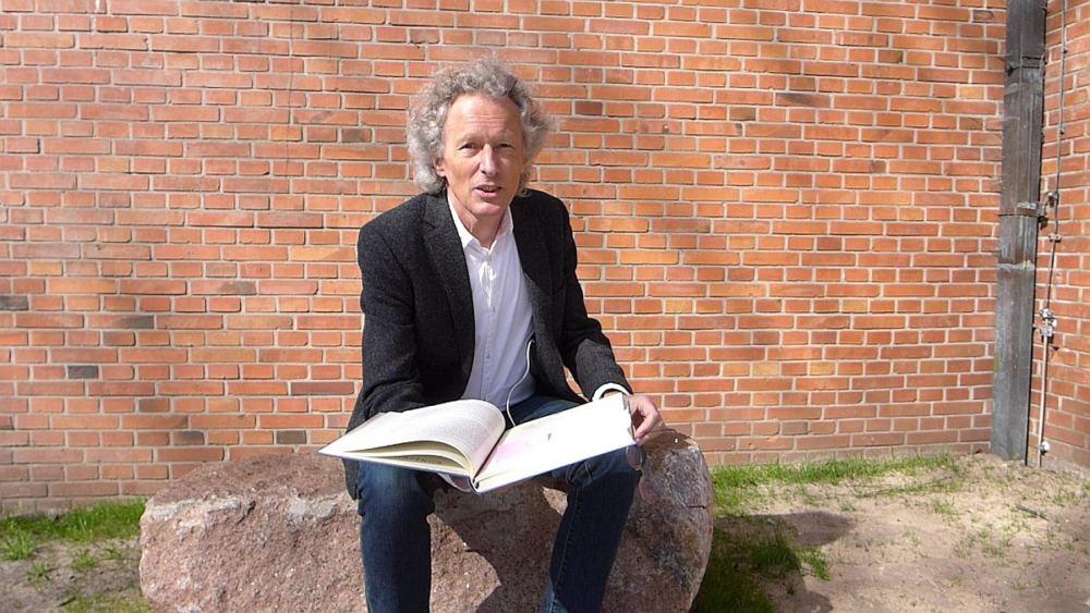 Pastor Janke sitzt auf einem Feldstein vor der Cornelius-Kirche